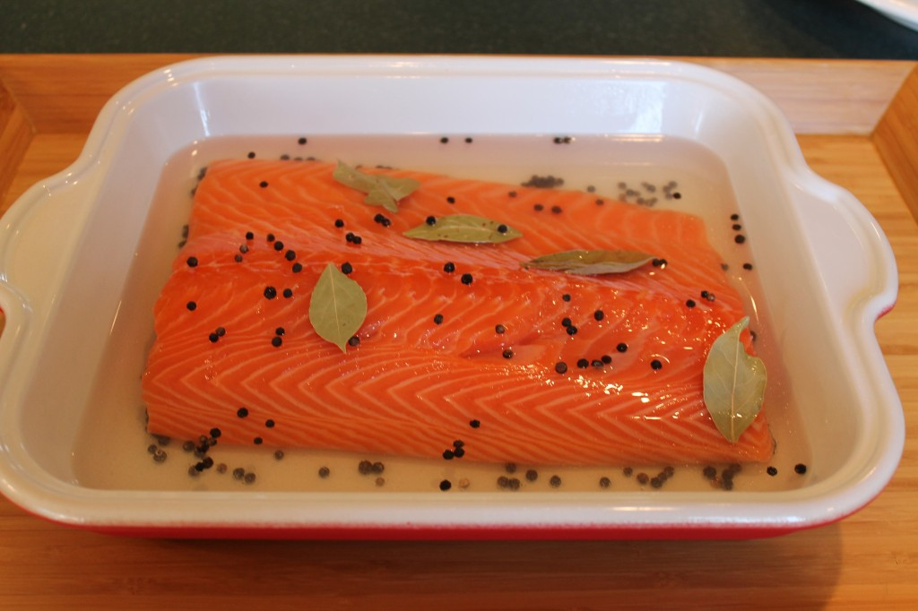 salmon in pan for poaching in white wine, peppercorns, bay leaves