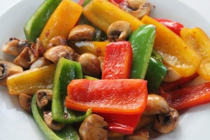 Saute pieces of cut up pieces of red, yellow and green peppers, quartered mushrooms, and red onion
