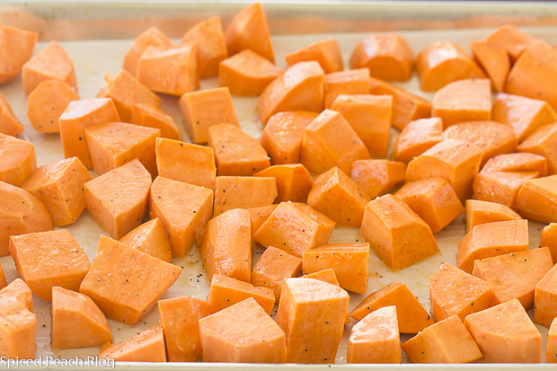Cubed sweet potatoes on parchment tossed with olive oil salt and pepper for roasting