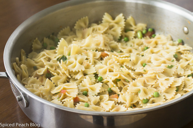 cooked bow tie pasta in skillet with vegetables