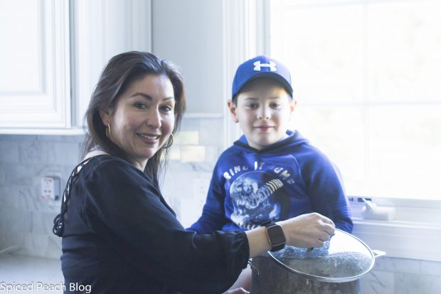 Alicia and son with a steaming pot of Ajiaco